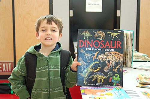 Photo of a male student holding up a large fold-out dinosaur book at MPTO's Book Exchange in the school cafeteria.