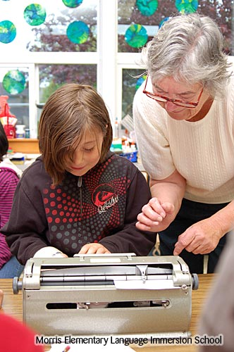 Photo of a student typing her name using a Braille machine as an adult assistant observes.